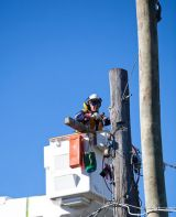ENERGEX worker in cherry picker working on power pole